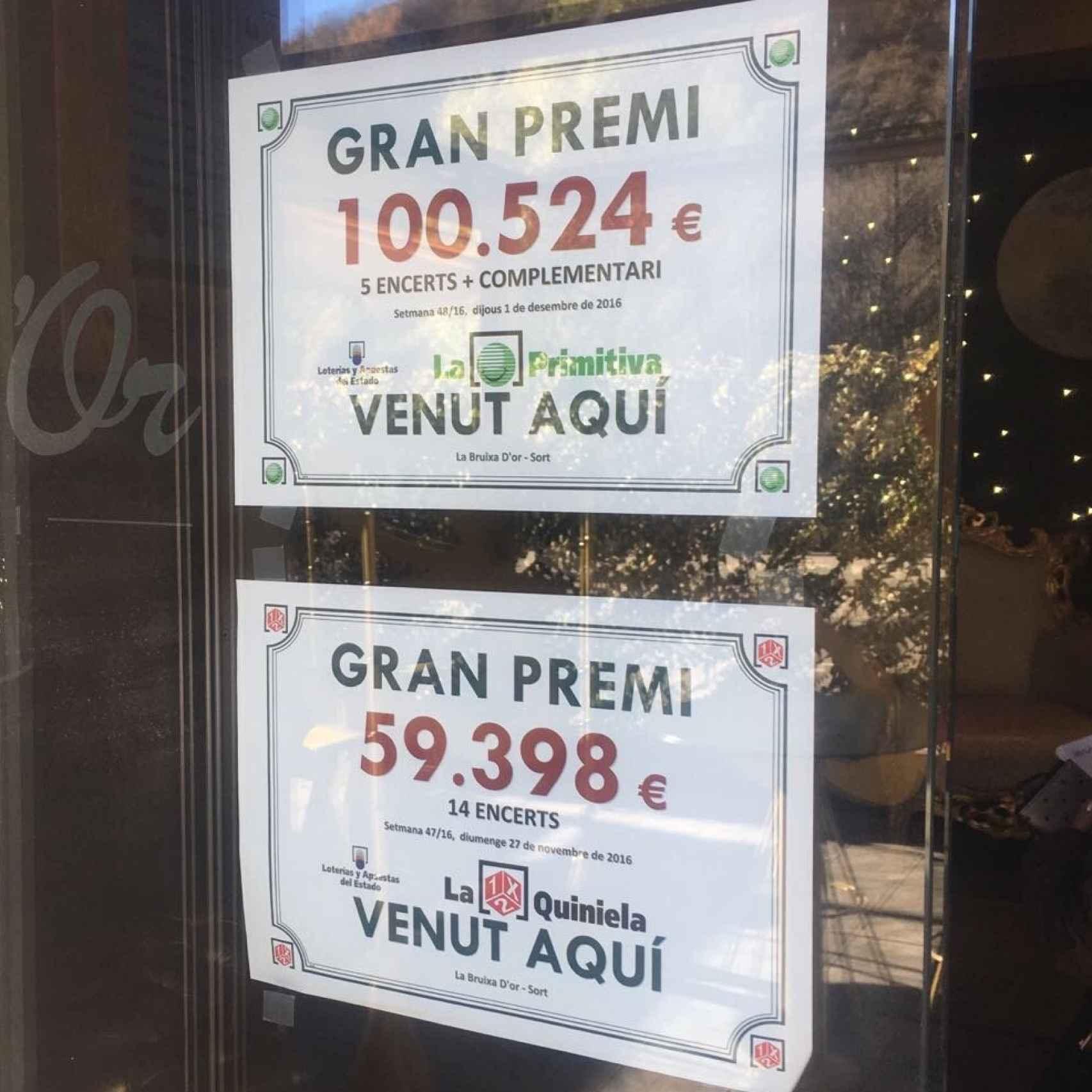 Carteles que anuncian la venta de décimos premiados en la puerta de La Bruixa d'Or