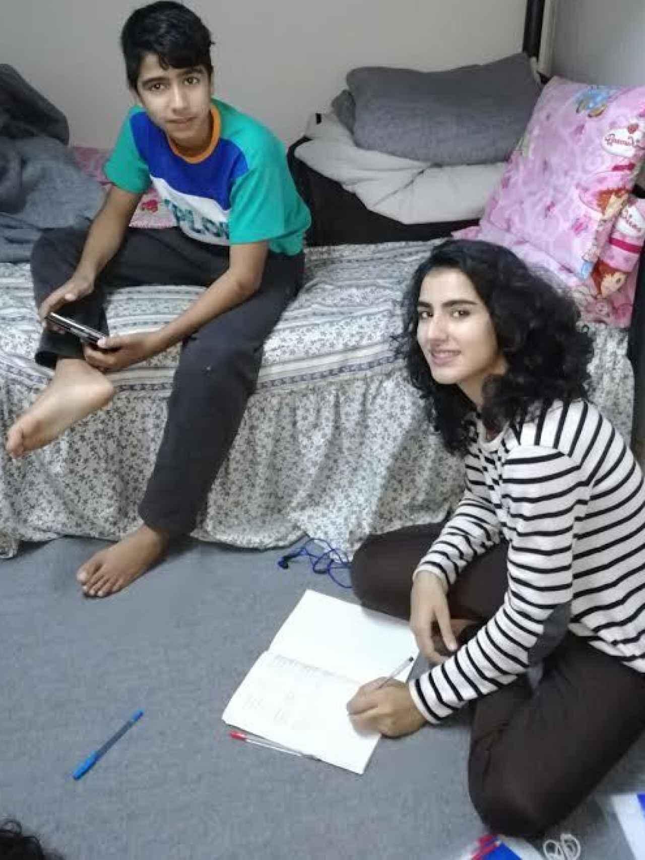 Sahar, con su hermano, no pierde la sonrisa en un campamento de refugiados de Grecia.