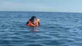Una mujer refugiada llora en medio del mar.