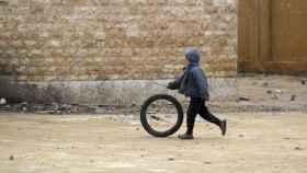 Un niño juega con una rueda en un colegio afectado por las bombas.