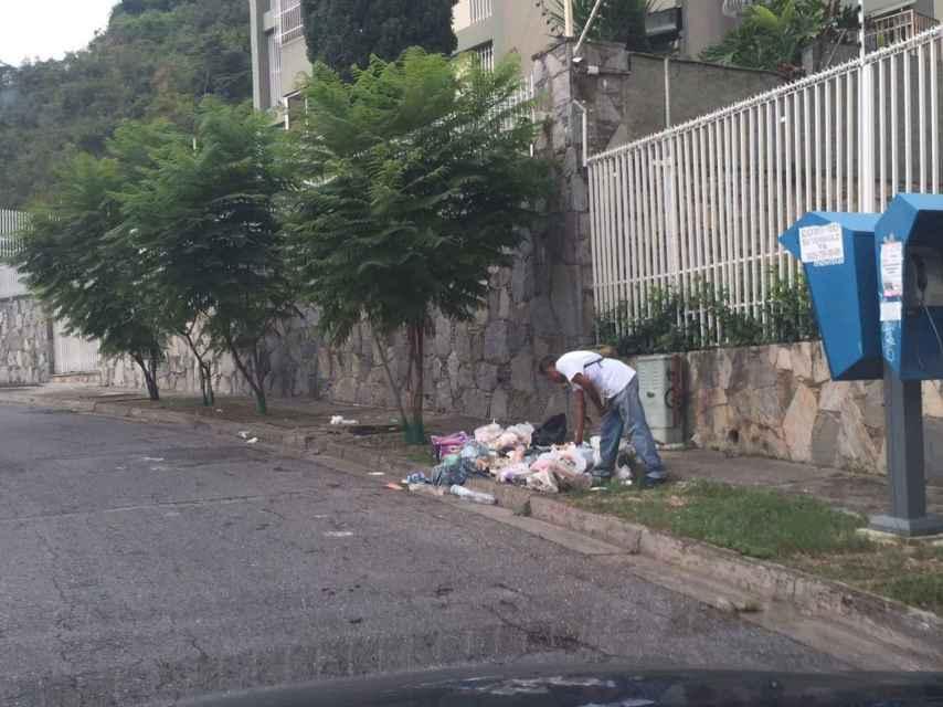 Un hombre buscando comida en la base en Caracas.
