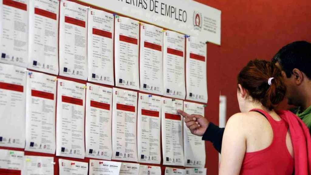 Una pareja consulta un tablón de ofertas de empleo.