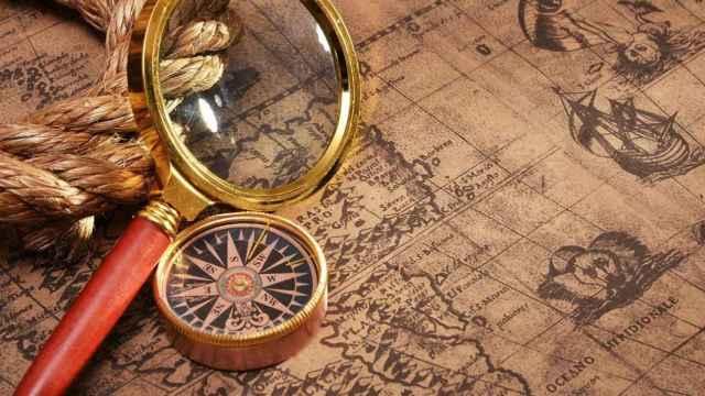 Una lupa y una brújula sobre un mapa.