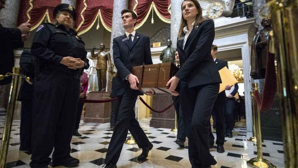 Bedeles del Senado transportan la urna que contiene los votos de las presidenciales.