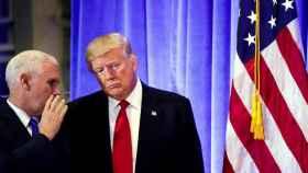 El vicepresidente electo, Mike Pence, habla con Trump durante una rueda de prensa.