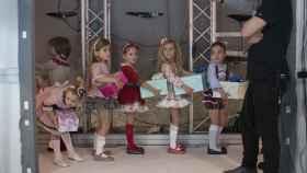 Unas niñas esperan su turno en el umbral de la pasarela