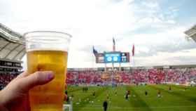 Un aficionado bebe una cerveza en un estadio de fútbol.