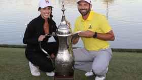 Angela Akins y Sergio García posan sonrientes junto al trofeo del golfista en Dubai.