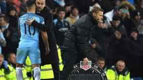 Guardiola saluda a Agüero en un partido del City.