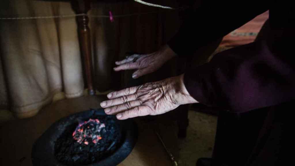 Una mujer se calienta las manos en un brasero de picón en Sevilla