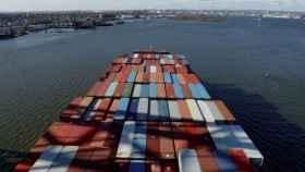 Un barco cargado de contenedores se dirige a un puerto para ser atendido por una empresa de estiba.