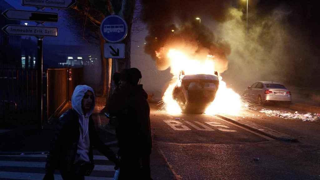 Un coche arde durante los enfrentamientos de manifestantes con policías en un suburbio de París.