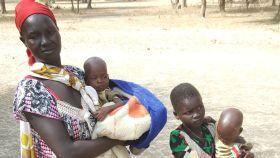 Nyayolah posa con sus hijos en un lugar seguro lejos de casa en Sudán del Sur.