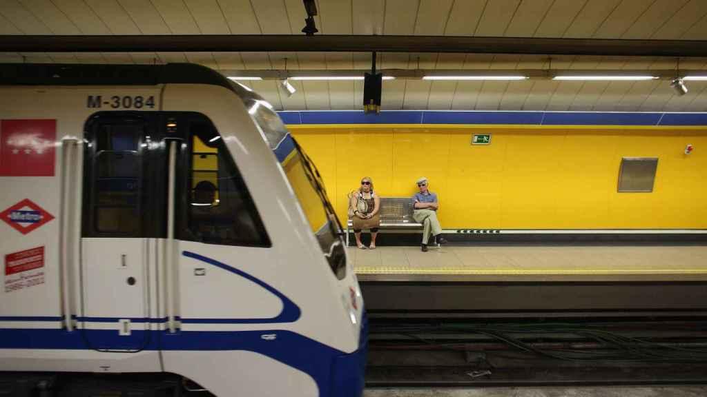 Dos pasajeros esperan al metro en una estación madrileña.