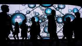 Varios visitantes ante una gran pantalla durante el Mobile World Congress (MWC).
