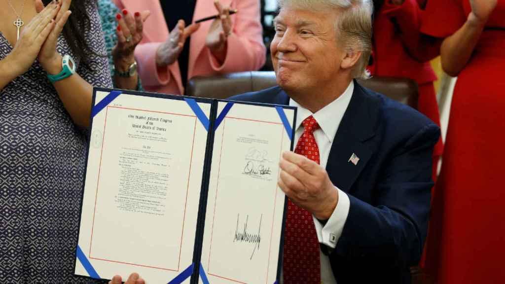 Trump muestra su firma estampada en la ley.