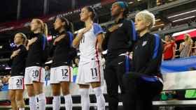 Megan Rapinoe escucha el himno nacional con una rodilla en el suelo.