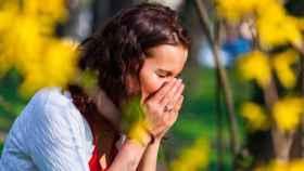 Una mujer se tapa la nariz y la boca para estornudar.