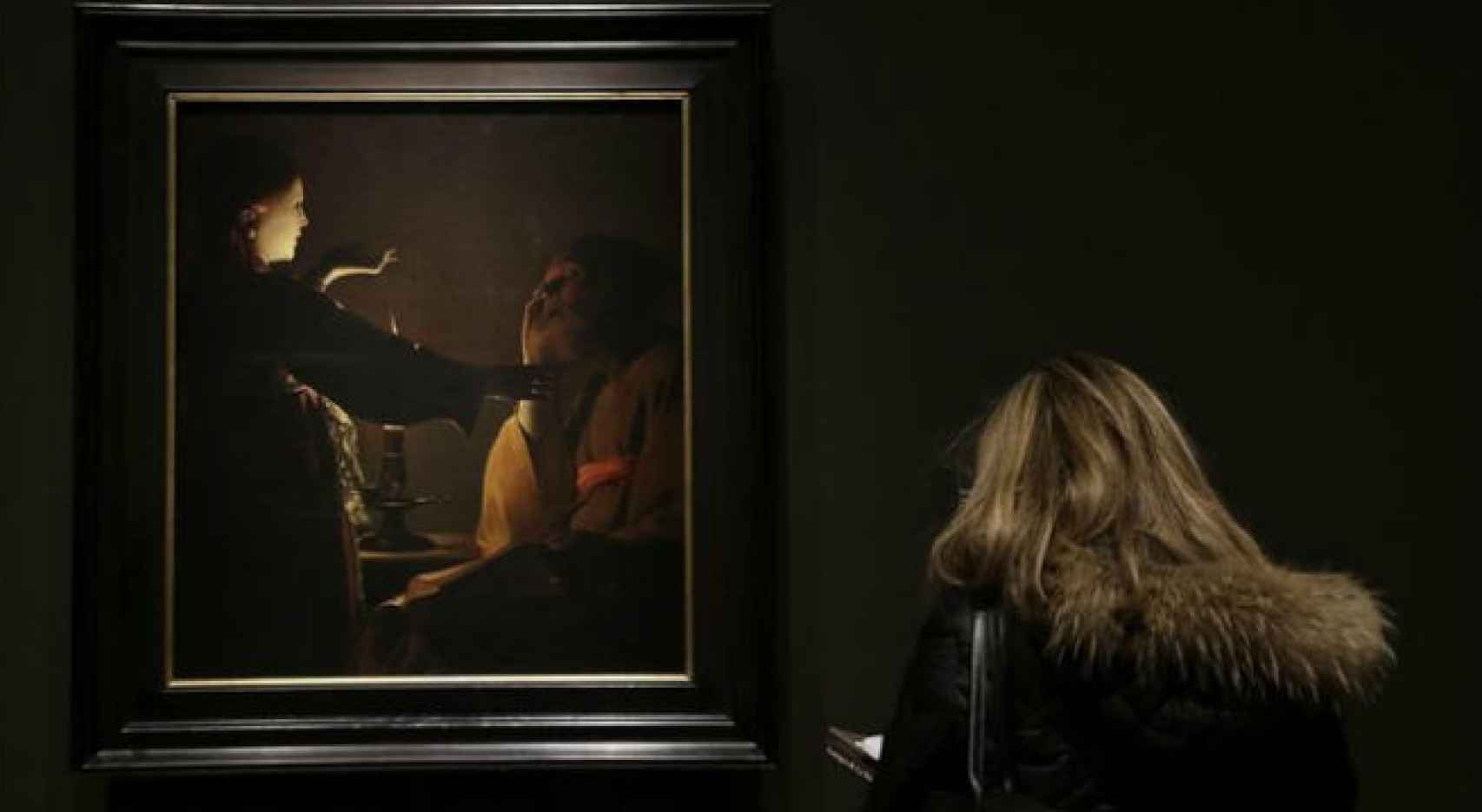 Visitante ante Aparicion del ángel san José, en la exposición de Georges de La Tour en el Prado.