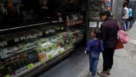 Una mujer y una niña pasan por delante de una tienda de comestibles en el centro de Caracas.