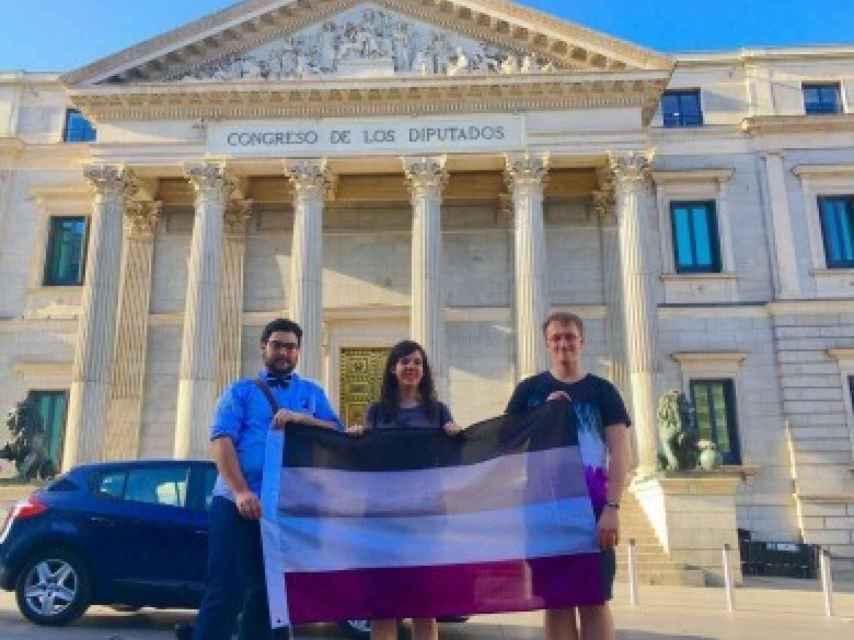 Alex junto con compañeros de ACE luciendo la bandera asexual en la puerta del Congreso.