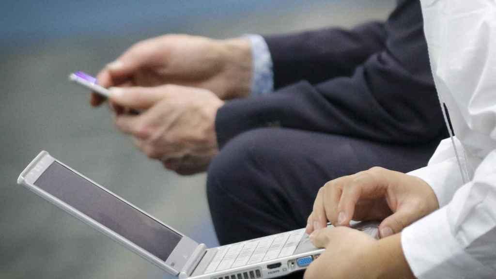 Lectores consultado sus dispositivos móviles, en una imagen de archivo.