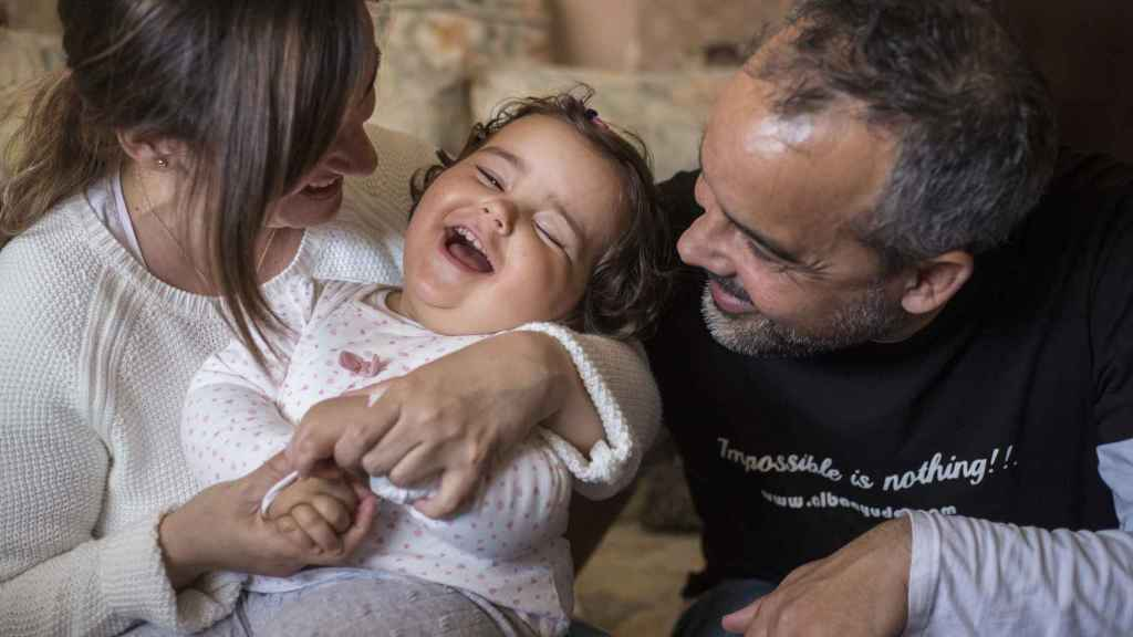 Alba, sonriente entre sus padres, Belén y Sergio.