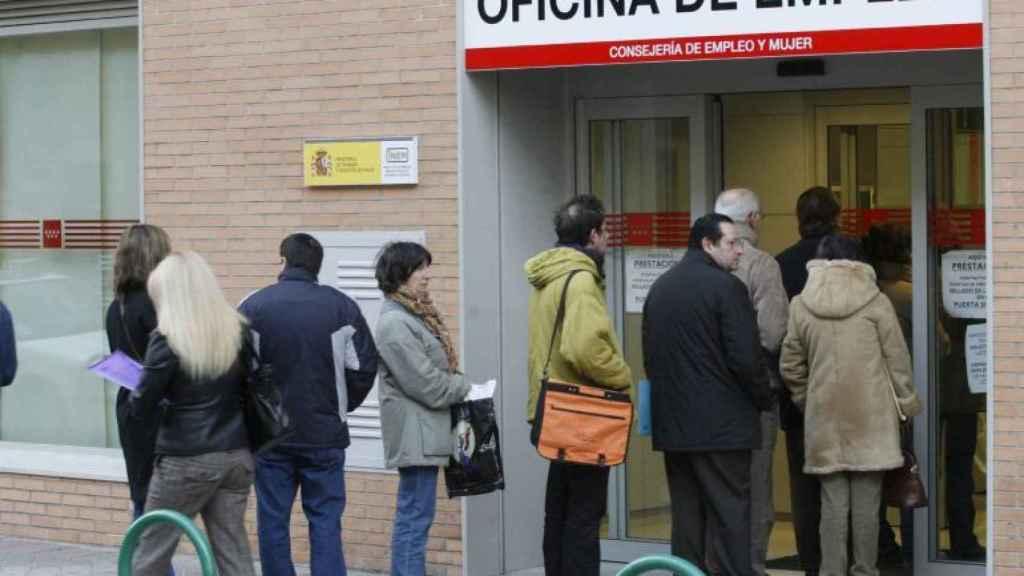 Un grupo de personas hacen cola en la entrada de una oficina de empleo.