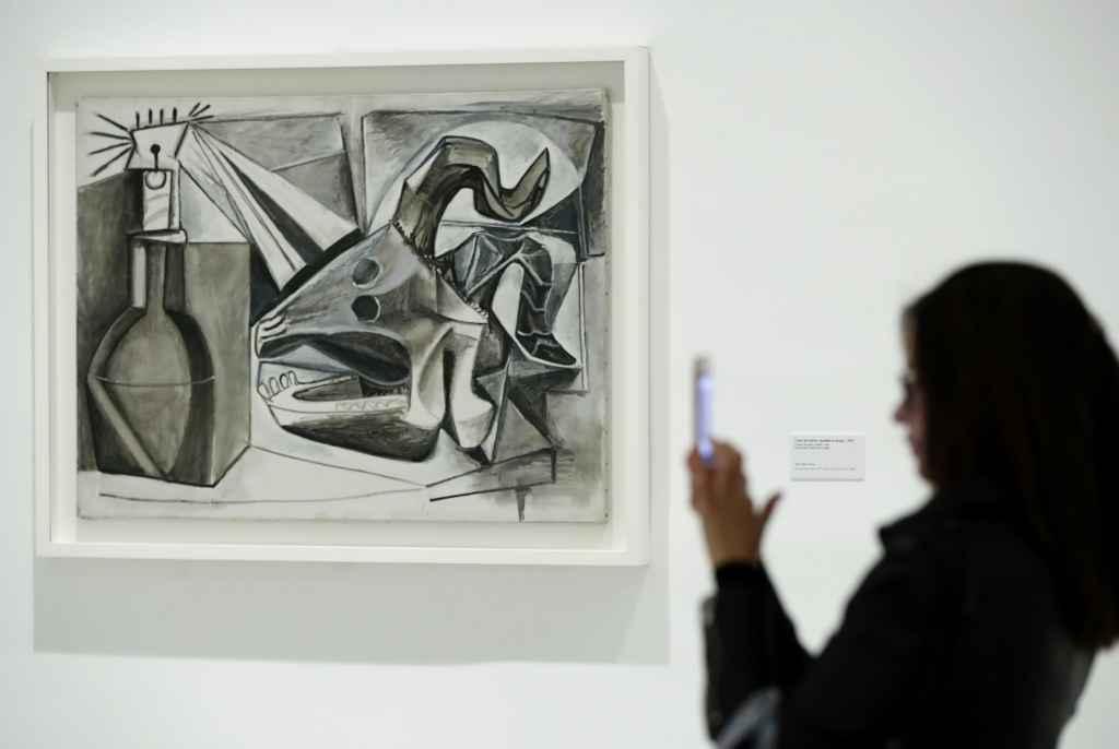 Una visitante frente a la obra de Picasso Cráneo de cabra, botella y vela, en el Museo Reina Sofía.