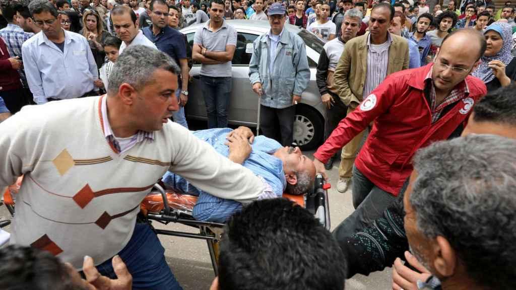 Varias personas trasladan a una de las víctimas del atentado de Tanta.