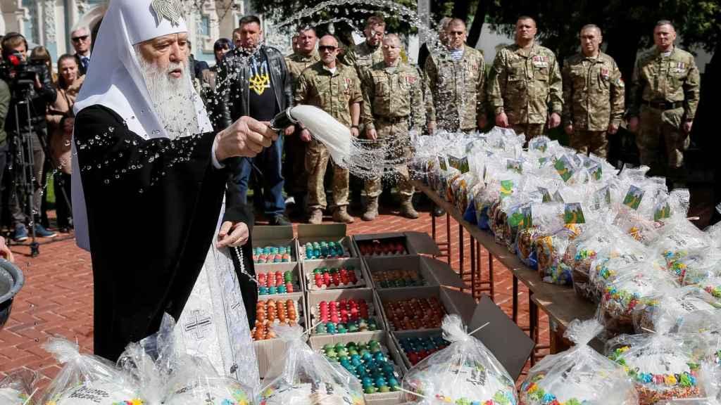 Un sacerdote de la Iglesia Ortoxoda de Ucrania vierte agua bendita sobre huevos de chocolate.