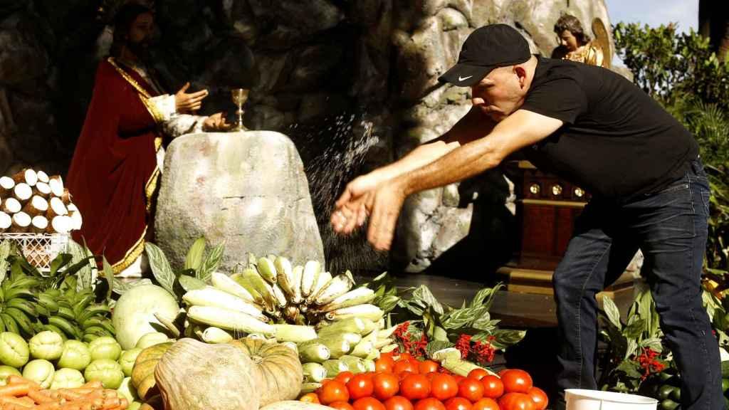 Hombre en Costa Rica vierte agua bendita sobre verduras donadas a los necesitados.
