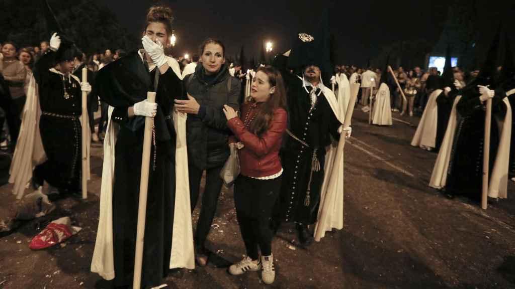 Una nazarena llora después de haber sufrido una de las estampidas que agitaron la 'Madrugá'