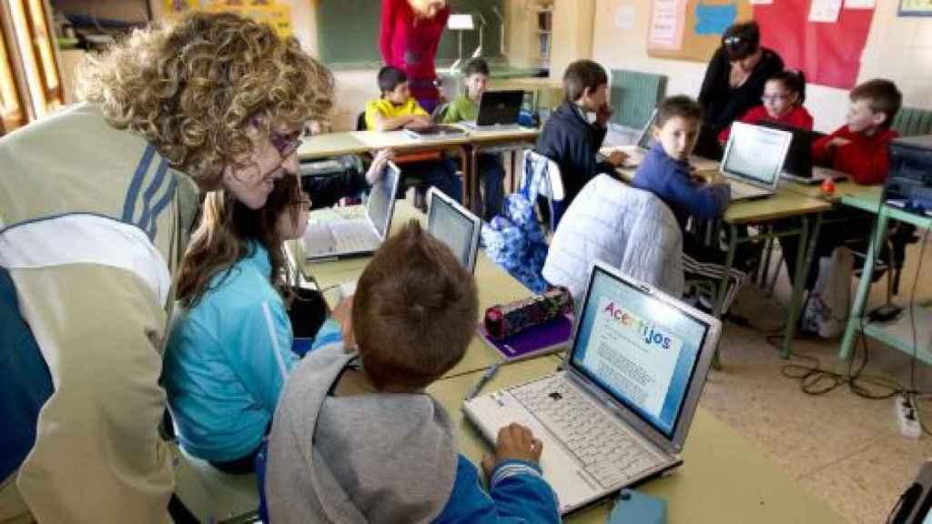 Varios niños en un aula con ordenadores.