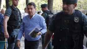 Ignacio González acompañado por varios agentes durante el registro en su oficina