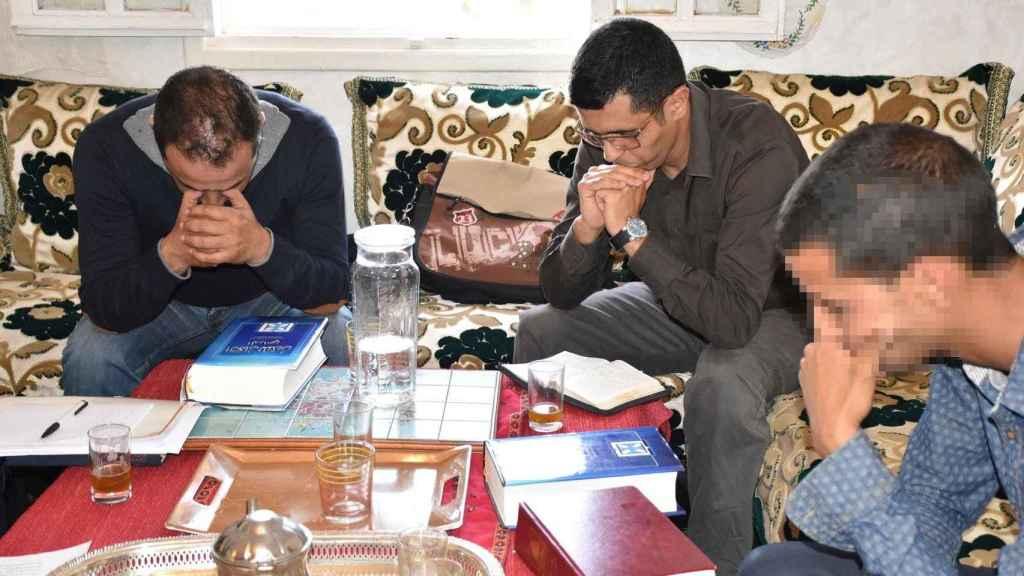 Las biblias en árabe descansan sobre la mesa mientras los conversos rezan.