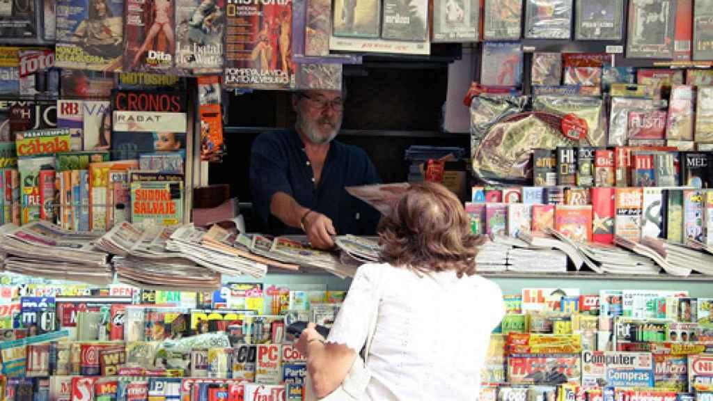 Una señora compra la prensa en un kiosko madrileño.