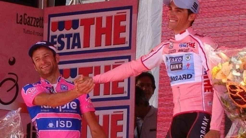 Michele Scarponi, en el podio del Giro 2011 saludando a Alberto Contador.
