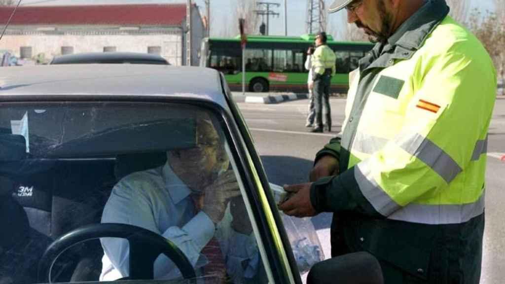 Un agente realiza un control de alcolhemia a un conductor.