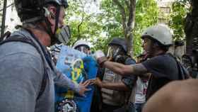 Miguel Gutiérrez (2d), es abordado por manifestantes durante una protesta el lunes.