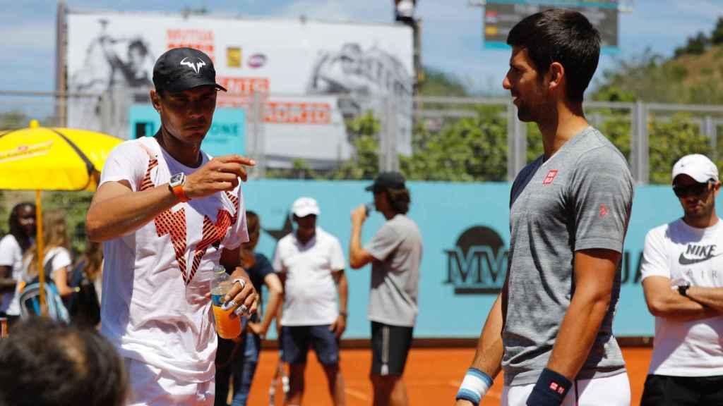 Djokovic y Nadal se saludan durante un entrenamiento en Madrid.