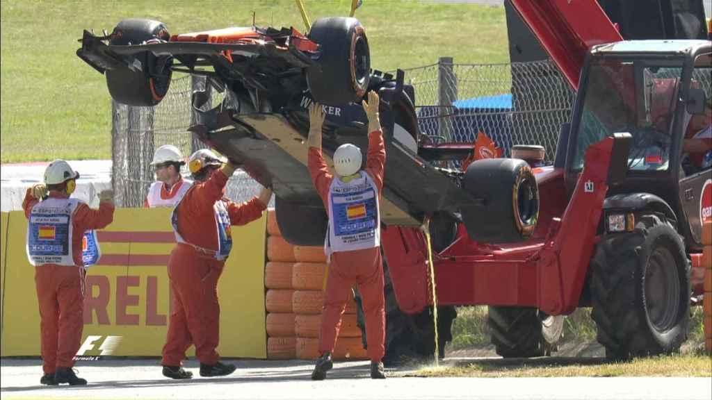 Los operarios retirando el coche de Alonso tras dos curvas.