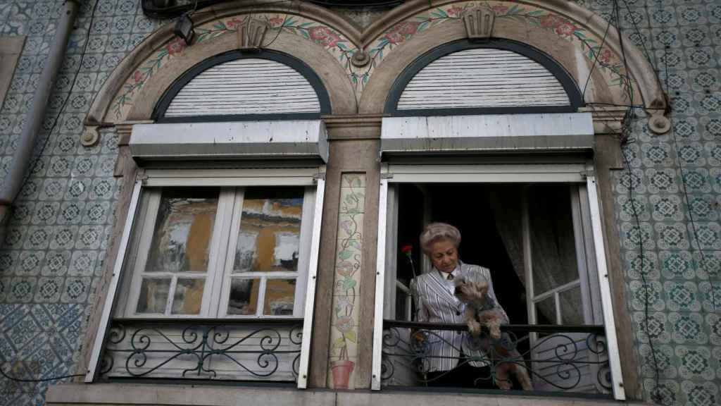 Una mujer junto a su mascota, en un balcón de Lisboa