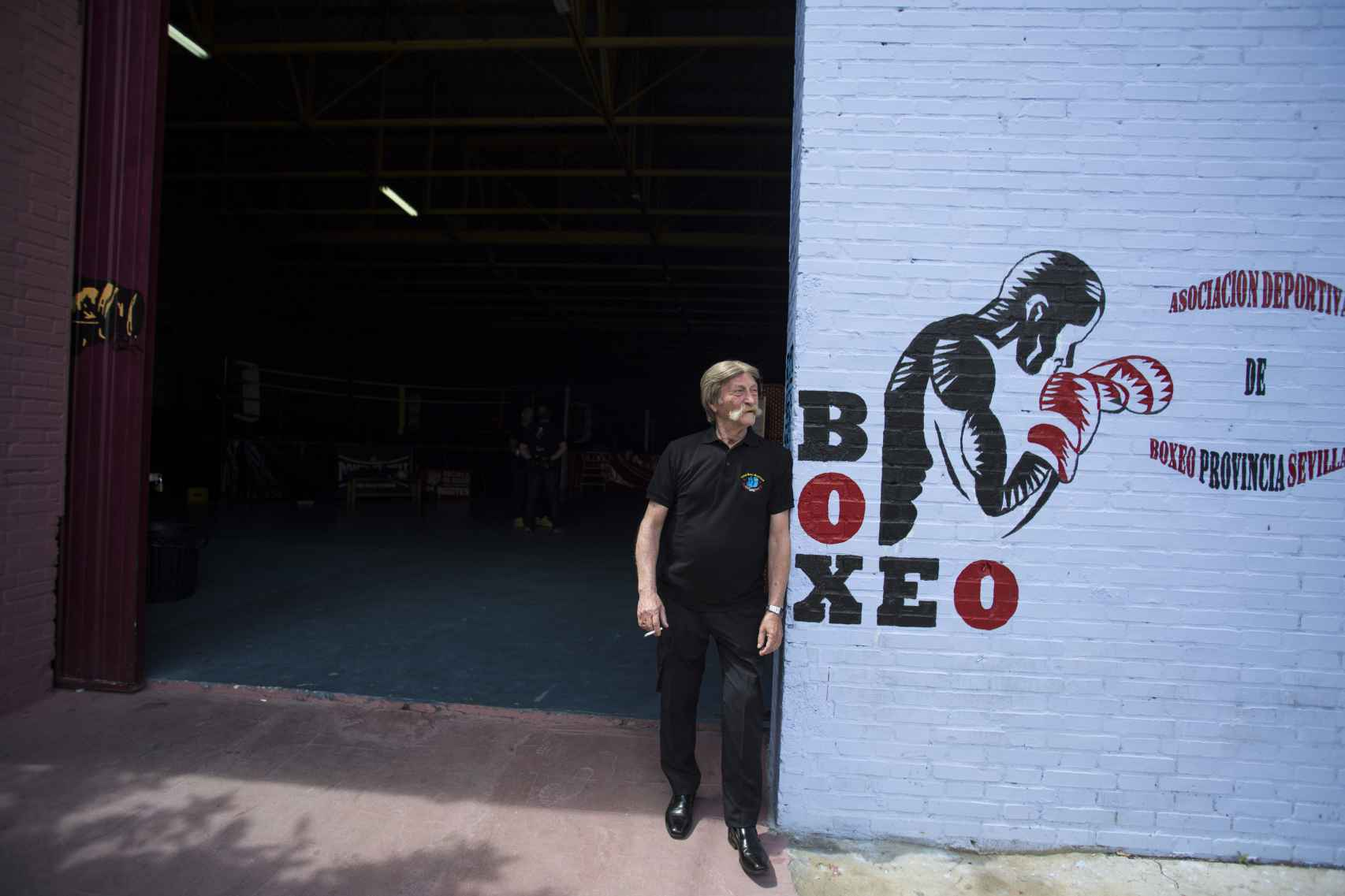 Antonio El Bigotes fumando un cigarrillo en la entrada a su centro de boxeo.