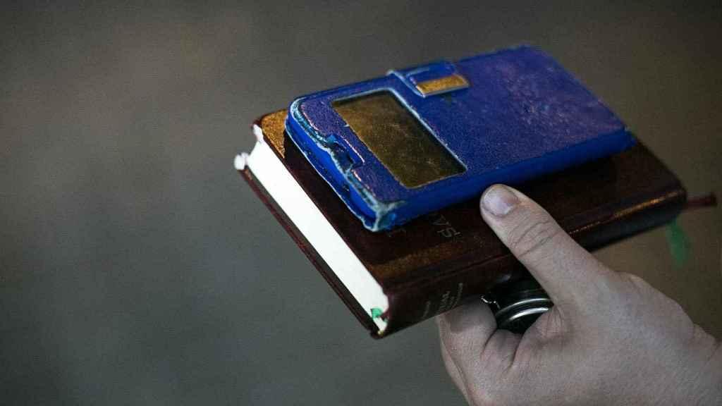 El móvil en el que el padre David atiende las llamadas de urgencia y su libro de sacramentos.