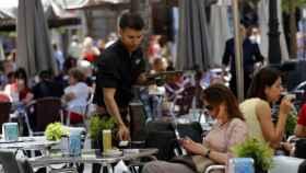 Un joven camarero sirve una consumición en una terraza.