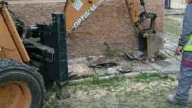 Una máquina excavadora levanta las losas originales de la acera de la plaza.