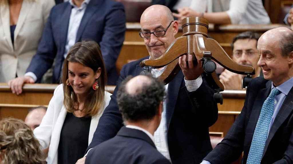El diputado de Ciudadanos Félix Álvarez, Felisuco, entrega a un ujier las patas rotas del escaño de Toni Roldán