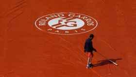 Un operario intentando achicar agua en una pista de Roland Garros.