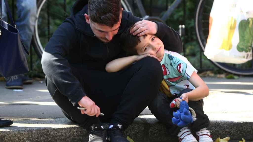 Un hombre consuela a su hijo tras ver cómo se ha incendiado la torre.